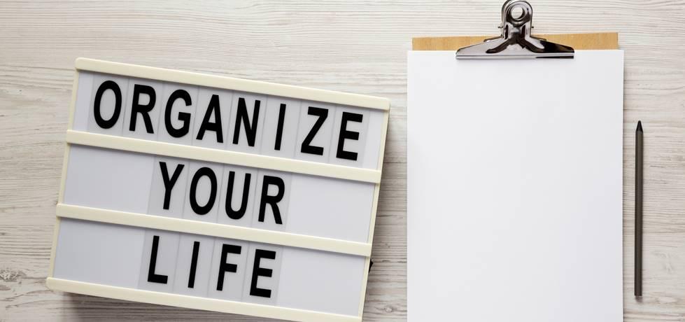 Escrito: Organize sua vida em uma mesa de luz e uma prancheta com folha de papel em branco