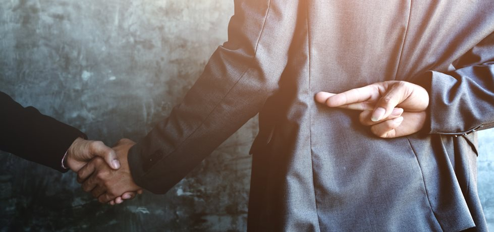 Pessoas de negócios apertando as mãos e um deles segurando os dedos cruzados atrás das costas