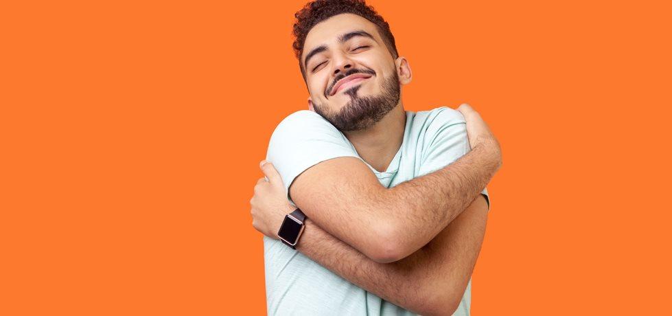 Homem abraçando-se e sorrindo