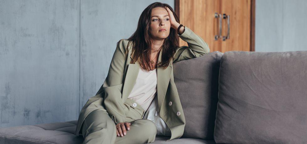 Mulher sentada no sofá pensativa