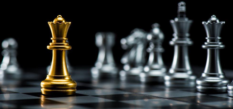Uma peça de xadrez dourada ficar contra o conjunto completo de peças de xadrez.