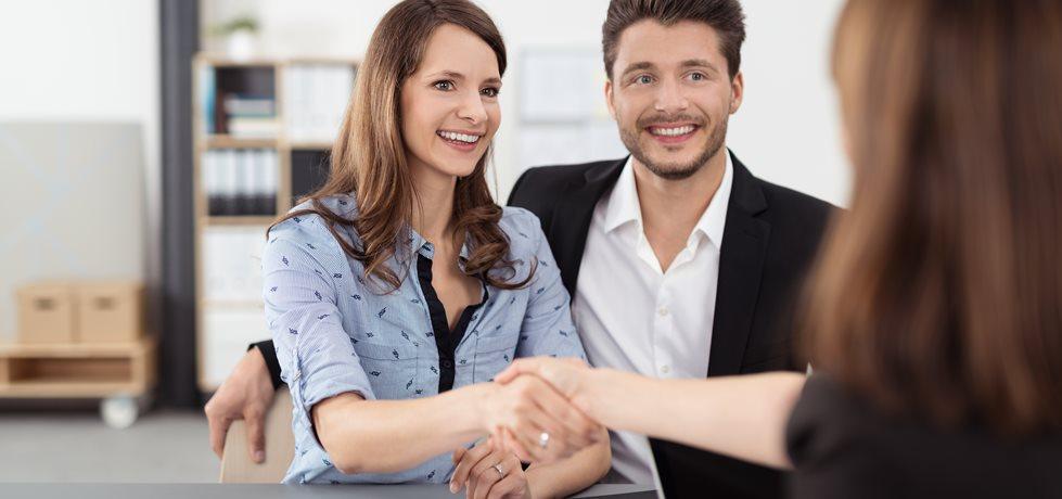 Casal feliz apertando as mãos de uma vendedora
